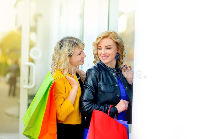 Dwa dziewczyny uśmiecha się trwanie pobliskiego sklepowego okno z torbami na zakupy obraz royalty free