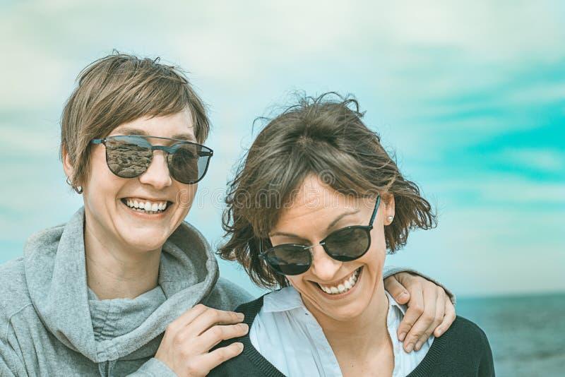 Dwa dziewczyny uśmiecha się zabawę na plaży i ma Zdrowy i rozochocony styl życia zdjęcie royalty free