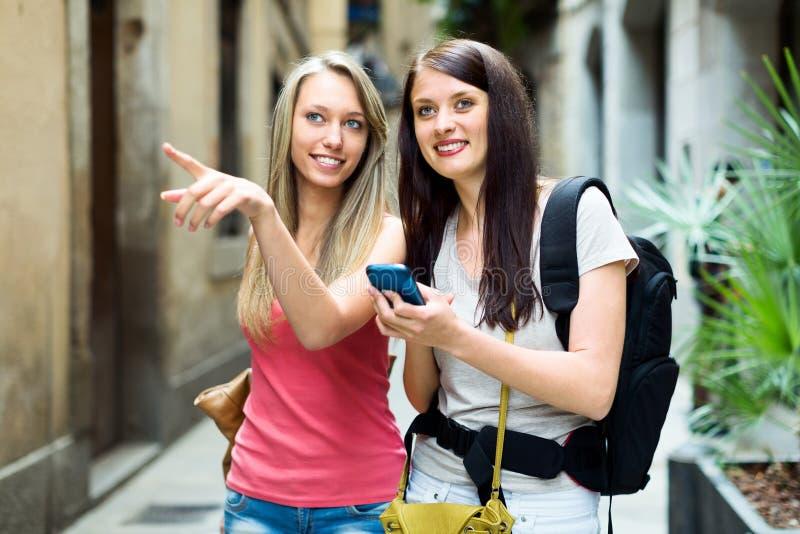 Dwa dziewczyny używa smartphone dla znajdują sposób obrazy stock