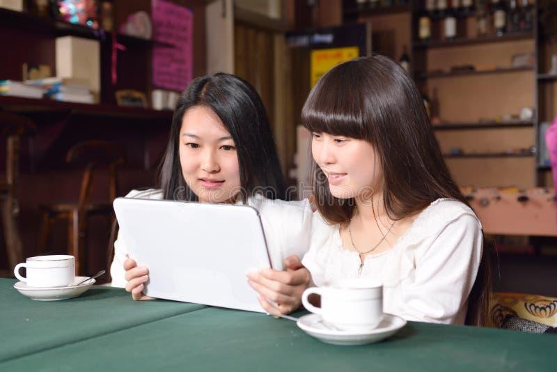 Dwa dziewczyny używają pastylkę w kawiarni zdjęcia stock