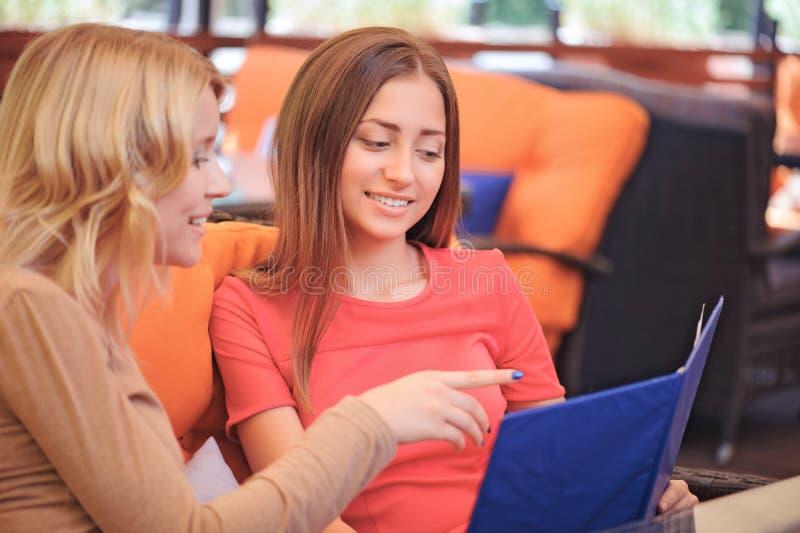 Dwa dziewczyny w cukierniany patrzeć przez menu fotografia stock