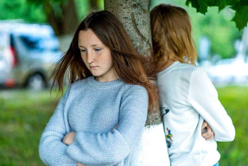 Dwa dziewczyny w lecie w parku Pojęcie szkolni przyjaciele w bełcie, problemowy nastolatek Emocje konflikt obraz stock