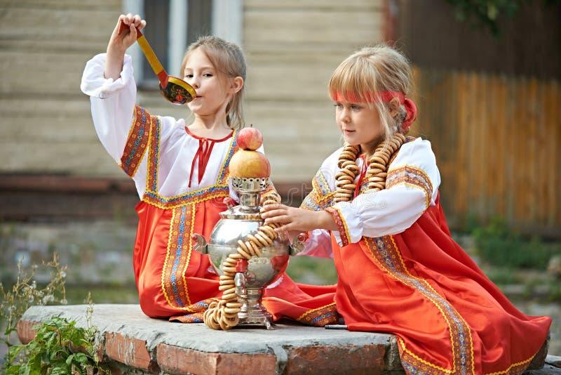Dwa dziewczyny w Rosyjskich krajowych kostiumach z samowarem zdjęcia stock