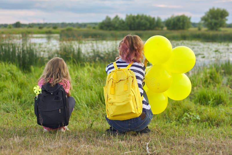 Dwa dziewczyny z balonami z powrotem w naturze, dzieci blisko jeziora zdjęcia stock