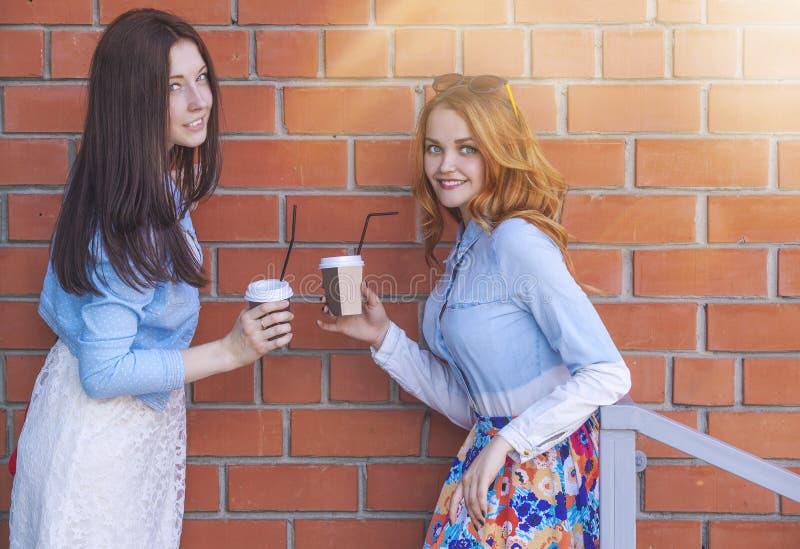 Dwa dziewczyny z filiżanki kawy rozmową obraz stock