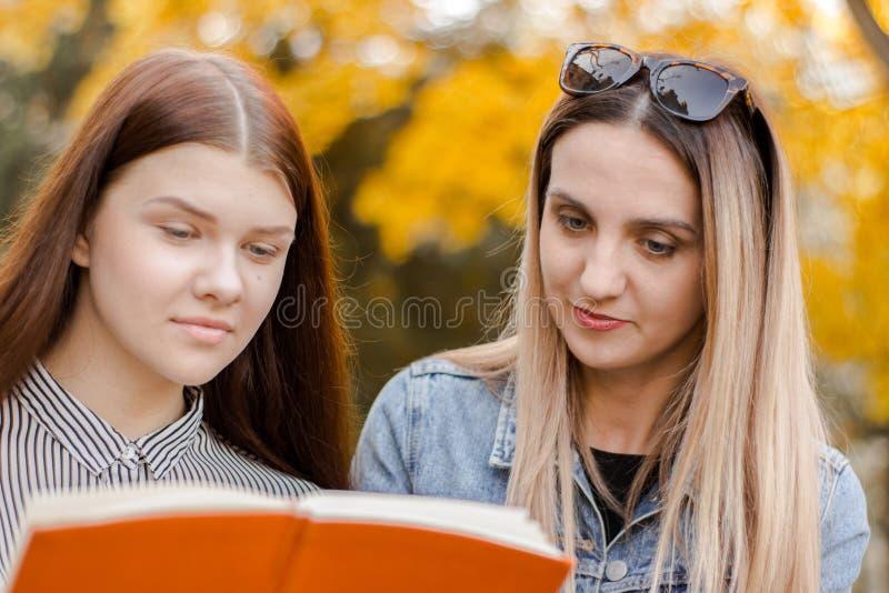 Dwa dziewczyny z przyjemnością, czytają książkę w jesień parku zdjęcie stock
