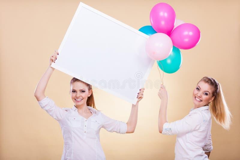Dwa dziewczyny z puste miejsce balonami i deską zdjęcie stock