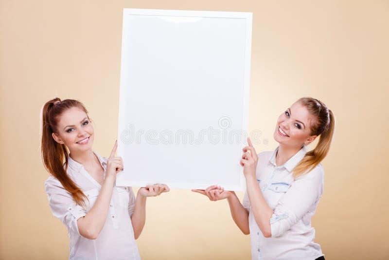 Dwa dziewczyny z pustej prezentaci deską zdjęcie royalty free