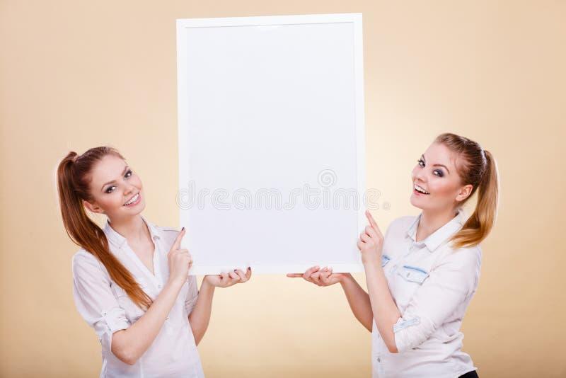 Dwa dziewczyny z pustej prezentaci deską fotografia royalty free