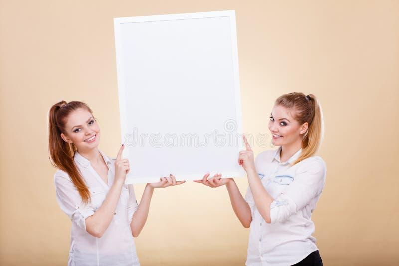 Dwa dziewczyny z pustej prezentaci deską obrazy stock