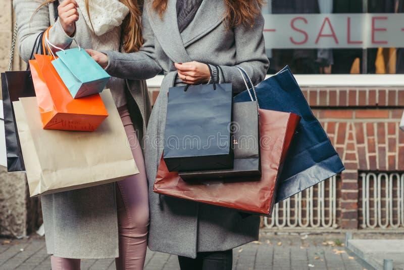 Dwa dziewczyny z torba na zakupy przed okno z sprzedażą pisać na nim fotografia royalty free