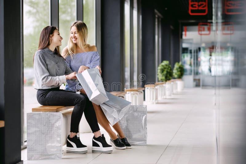 Dwa dziewczyny z zakupy obsiadaniem na ławce w centrum handlowym zdjęcia royalty free