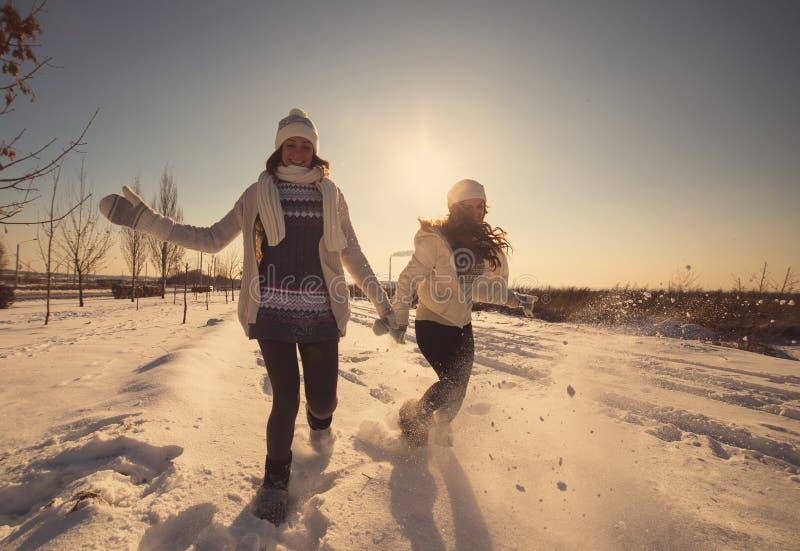 Dwa dziewczyny zabawę i cieszą się świeżego śnieg obrazy royalty free