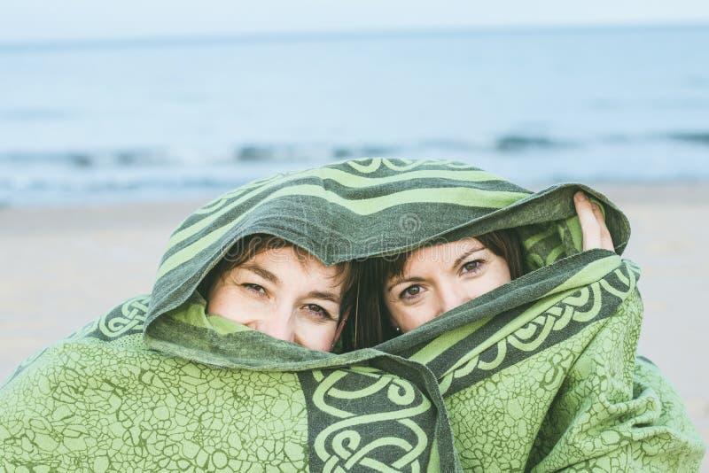 Dwa dziewczyny zakrywającej z koc Kobiety zakrywać z przesłoną i tajemniczym spojrzeniem obrazy royalty free