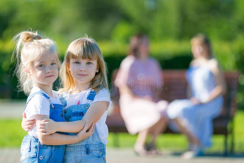 Dwa dziewczyny zostać przyjaciółmi i obejmowali podczas gdy ich matki opowiadają fotografia royalty free