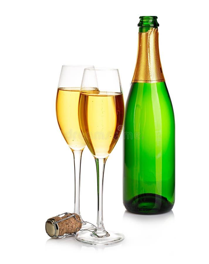 Dwa eleganckiego szampańskiego szkła na tle zielony butelki zakończenie odizolowywający na bielu wciąż świąteczny życie obrazy royalty free