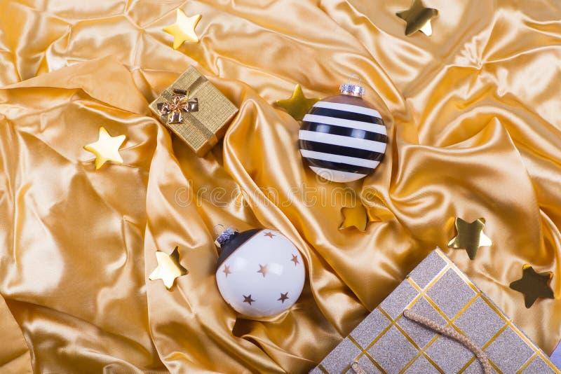 Dwa eleganckiej czarny i biały Bożenarodzeniowej piłki z gwiazdami, paski, prezenta pudełko i torba na złotej atłasowej tkaninie, obraz royalty free