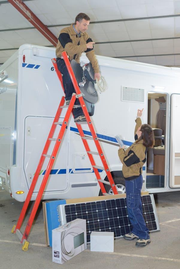 Dwa elektryka instaluje panel słoneczny na rv dachu obrazy royalty free