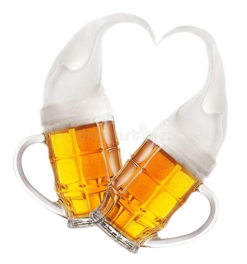 Dwa faceted kubka piwo z pluśnięciami piana w kształcie serce obrazy royalty free