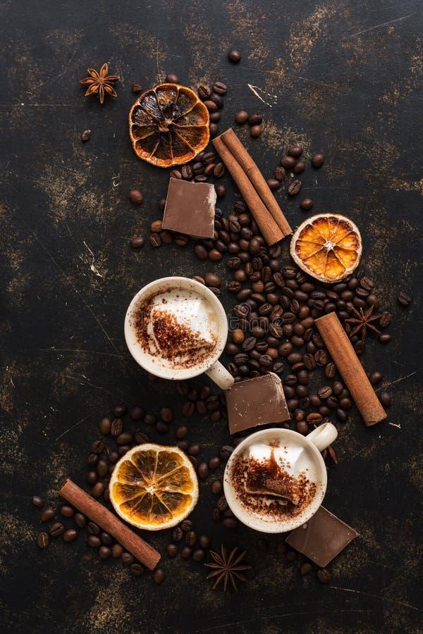 Dwa filiżanka kawy na ciemnym tle z piec kawowymi fasolami, cynamonowymi kijami i pokrojoną pomarańcze, overhead obraz royalty free