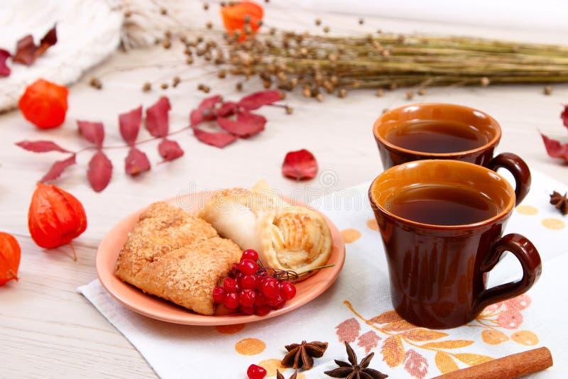 Dwa filiżanki brąz glina z herbatą są na białej bieliźnianej pielusze Maseł ciastka z owocowym dżemem i tortem z chałupa serem są obraz royalty free