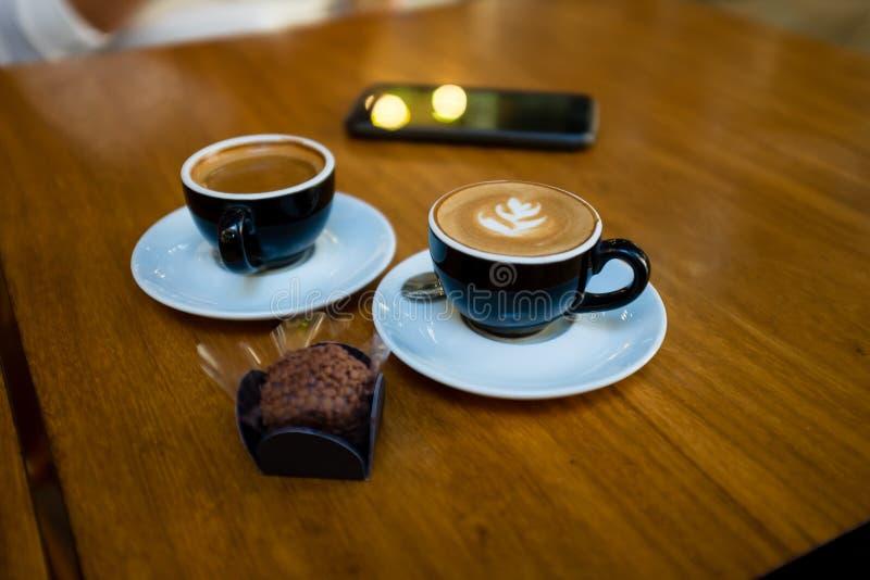 dwa filiżanki cappuccino na czarnych filiżankach na drewnianym stole z typowym brasilian cukierki, dzwonili brigadeiro Telefon ko zdjęcia stock
