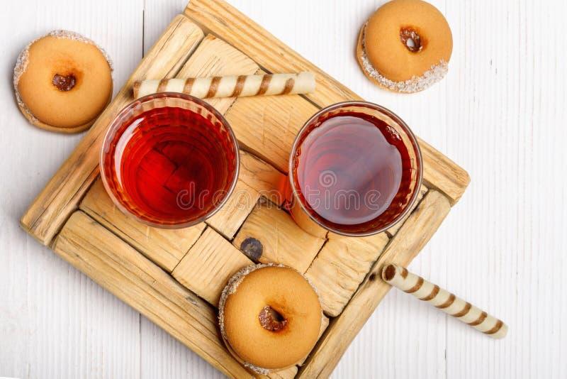 Dwa filiżanki gorąca herbata z wyśmienicie ciastkami na białym drewnianym stole fotografia stock