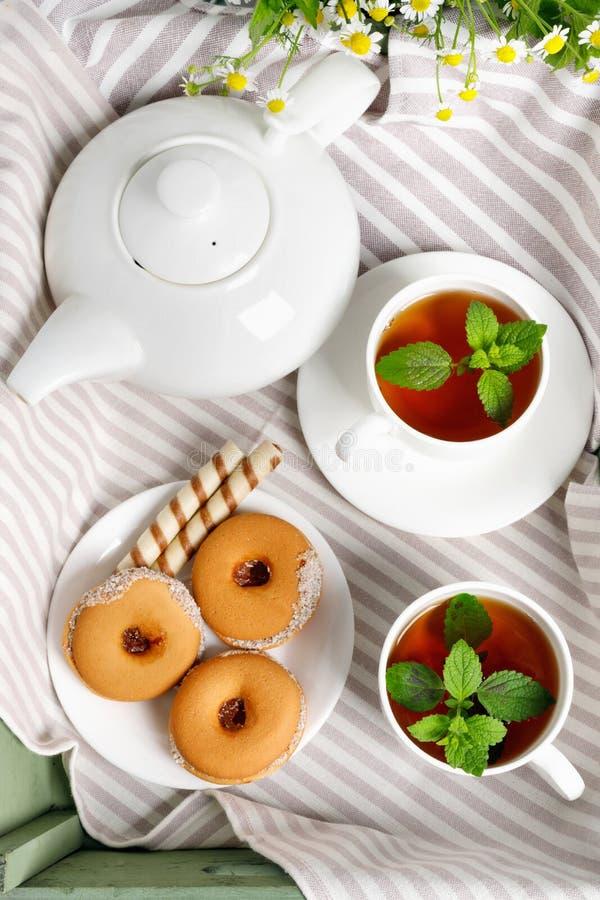 Dwa filiżanki gorąca herbata z wyśmienicie ciastkami na białym drewnianym stole fotografia royalty free