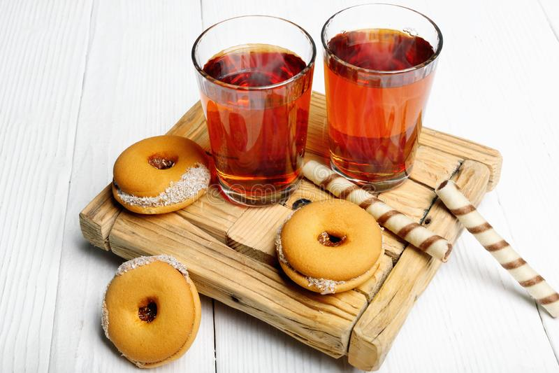 Dwa filiżanki gorąca herbata z wyśmienicie ciastkami na drewnianym stole zdjęcia royalty free