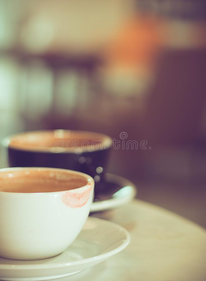 Dwa filiżanki gorąca kawa przy kawiarnią, biel jeden z czerwoną pomadki oceną zdjęcie royalty free