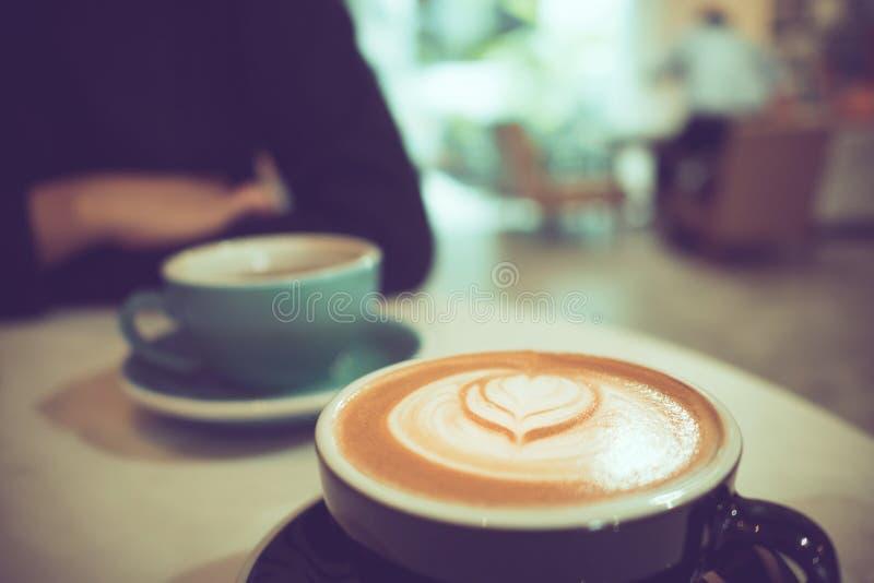 Dwa filiżanki gorąca kawa przy kawiarnią, jeden z kierową kształta latte sztuką obraz stock