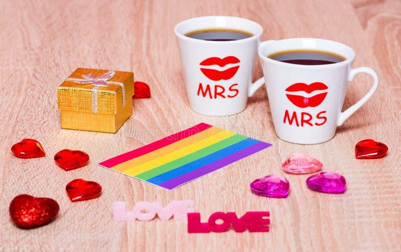Dwa filiżanki kawy, homoseksualista flaga i prezenta pudełko z małżeństwem, dzwonią fotografia royalty free