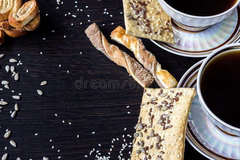 Dwa filiżanki kawy z ptysiowymi ciastami z słonecznikowymi ziarnami, sezamowymi ziarnami i lnem, Ostrość mała głębia obraz royalty free