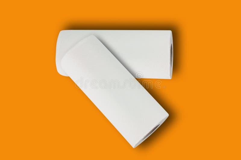 Dwa folującej rolki biali papierowi ręczniki miękki papier dla toalety w centrum na pomarańcze stole lub obraz royalty free