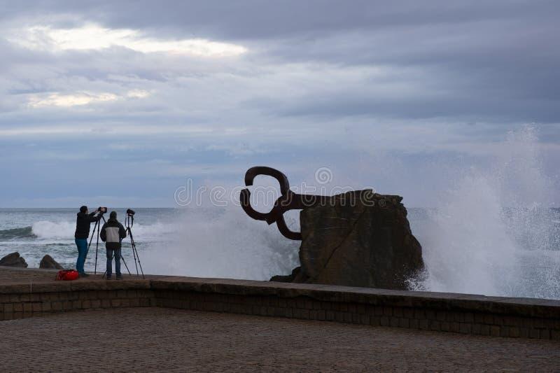 Dwa fotografa w El Peine De Los Vientos w mieście San Sebastian zdjęcie stock