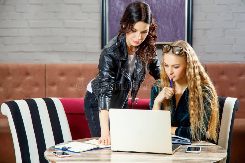 Dwa freelancers dyskutują nowych projekty z urządzeniami elektronicznymi podczas gdy siedzący w kawiarni obrazy royalty free
