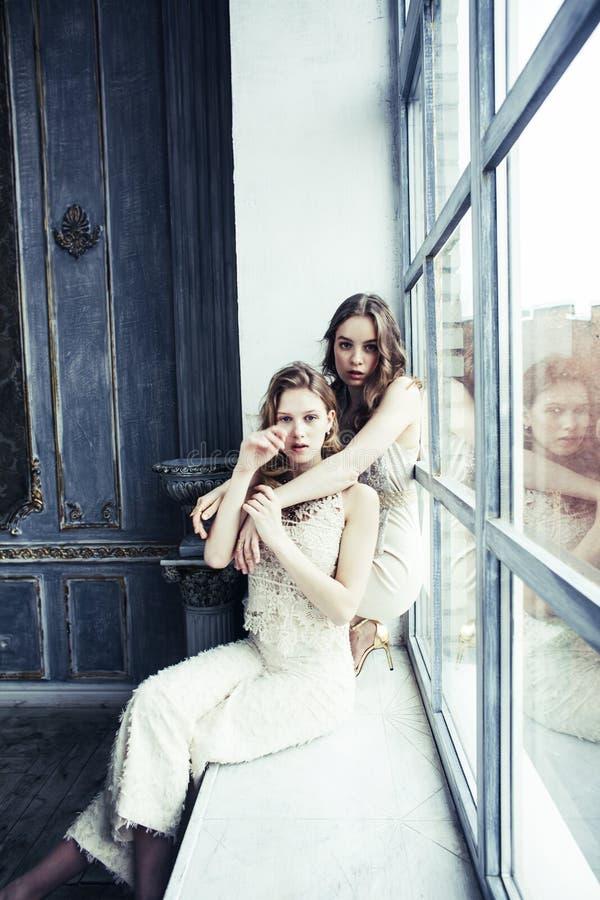 Dwa fryzury ładna bliźniacza siostrzana blond kędzierzawa dziewczyna w luksusowy hous obrazy stock