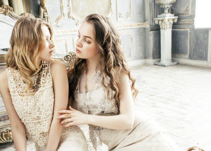 Dwa fryzury ładna bliźniacza siostrzana blond kędzierzawa dziewczyna w luksusu domu wnętrzu wpólnie, bogaci młodzi ludzie pojęć zdjęcie stock