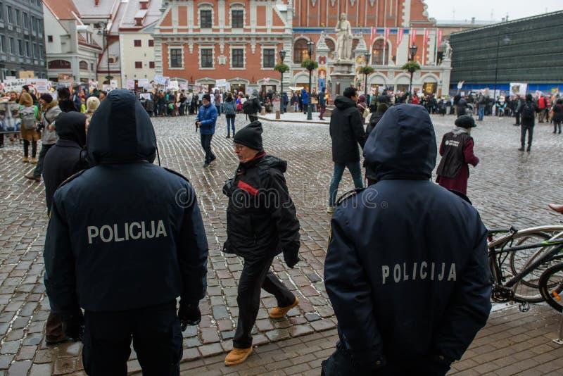 Dwa funkcjonariusza policji stoi przed tłumem z uczestnikami «Marzec dla zwierząt w Ryskim, Latvia fotografia royalty free