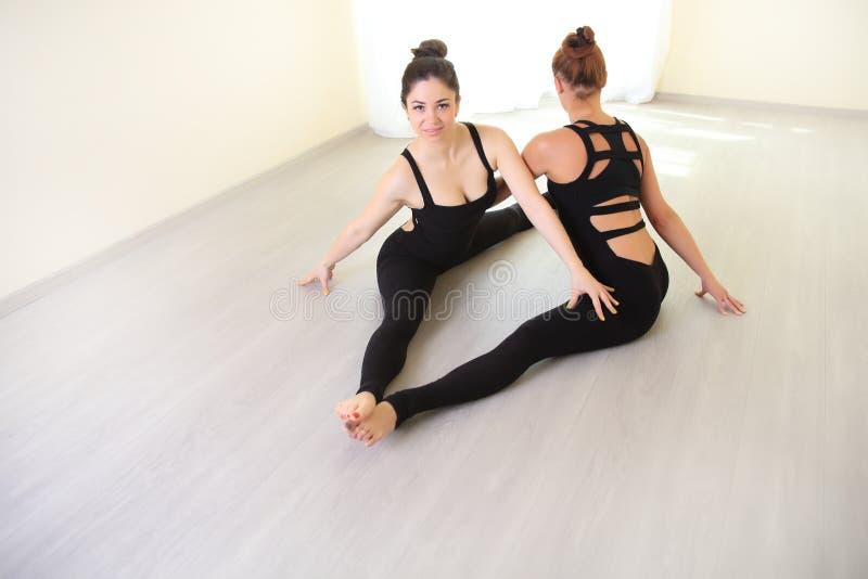 Dwa gimnastyczki kobiety robi rozciąganiu ćwiczą w białym wnętrzu obraz stock