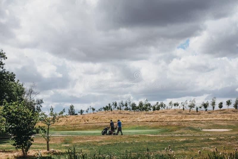 Dwa golfisty chodzi przez smołę na polu golfowym w Leicester z golfowymi powozikami, UK obrazy stock