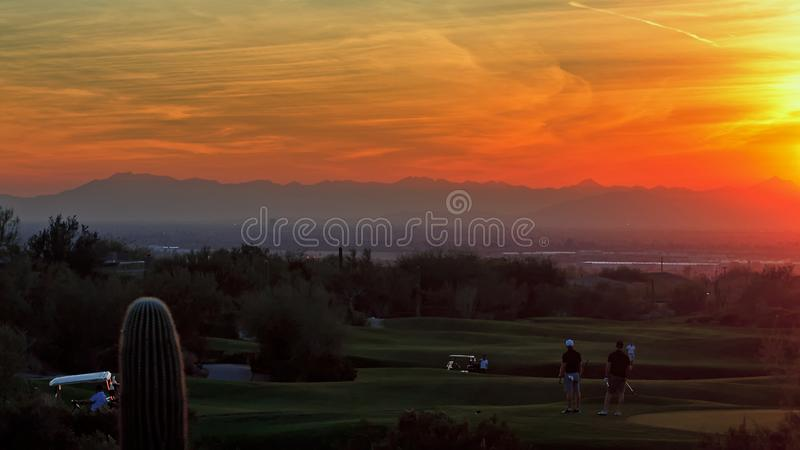 Dwa golfisty oglądają kolorowego zmierzch przy kijem golfowym w mesach, Arizona obrazy stock