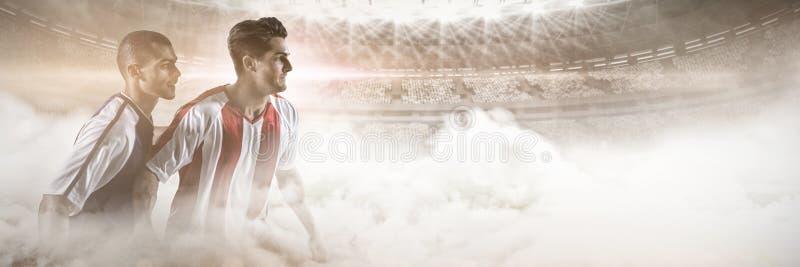 Dwa gracza futbolu broni each inny podczas gdy bawić się piłkę nożną przeciw graficznemu wizerunkowi stadium przy d fotografia royalty free