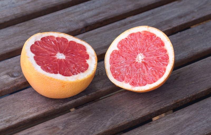Dwa grapefruitowej połówki na drewnianym tle zdjęcie stock