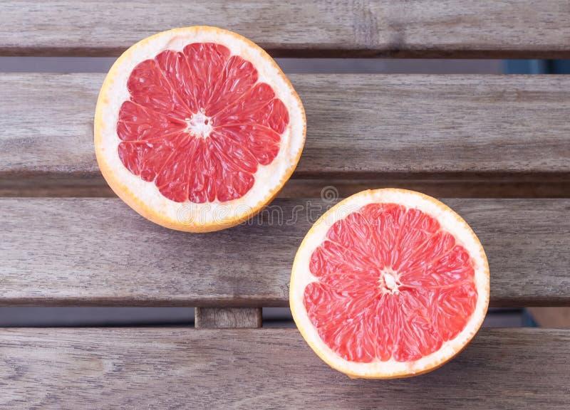Dwa grapefruitowej połówki na drewnianym tle fotografia royalty free