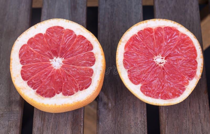 Dwa grapefruitowej połówki na drewnianym tle fotografia stock
