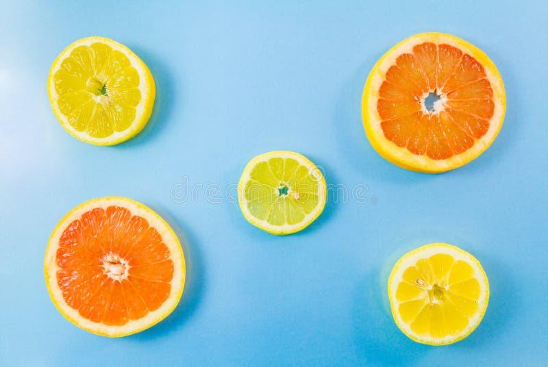 Dwa grapefruitowy i cytryno trzy plasterka na błękitnym tle fotografia royalty free