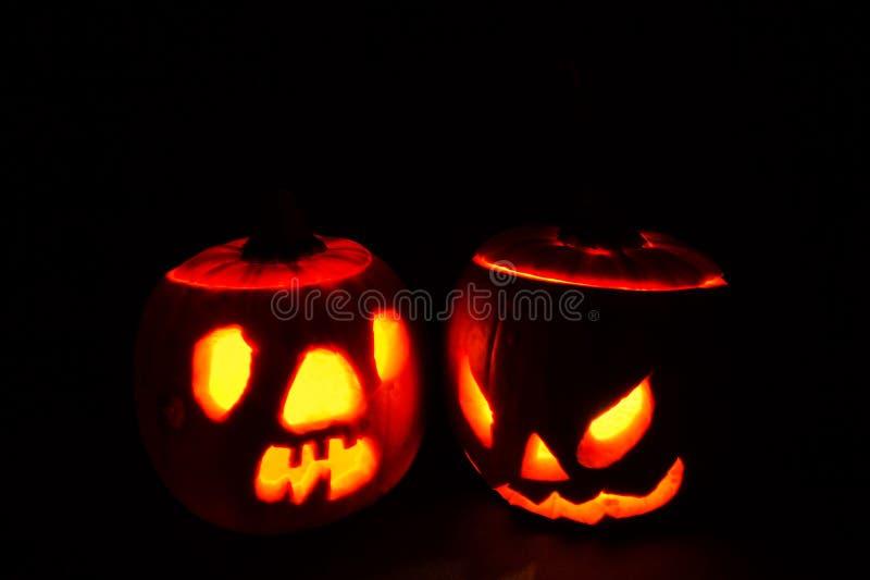 Dwa Halloweenowych rozjarzonych bani odosobniony ciemny tło zdjęcia stock