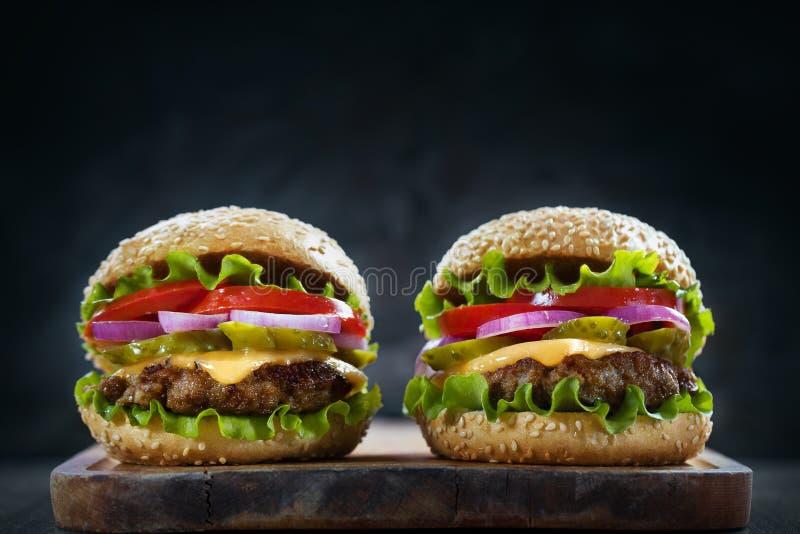 Dwa hamburgeru na nieociosanej drewnianej desce fotografia royalty free