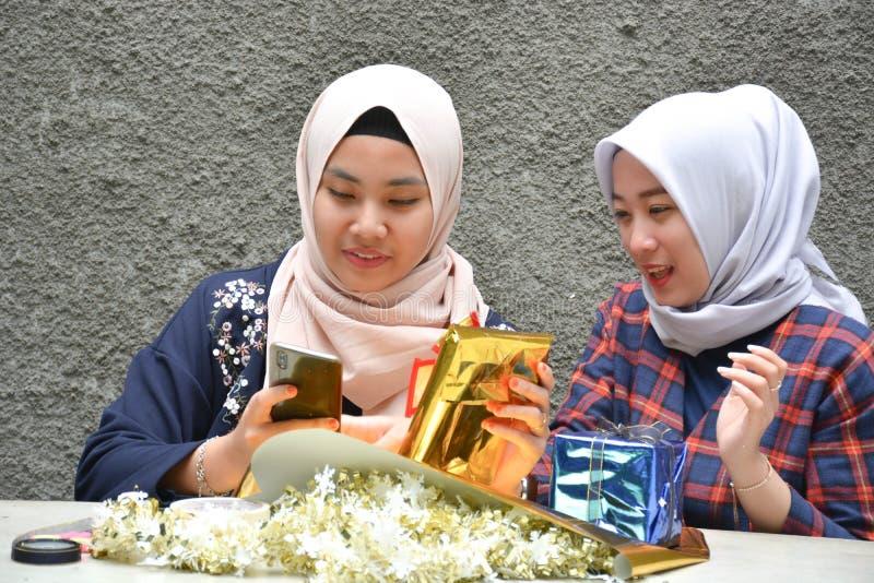 Dwa hijab bestfriend narządzania prezent siedzi wpólnie przy betonowym stołem obraz stock